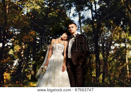 bride and groom standing in the park