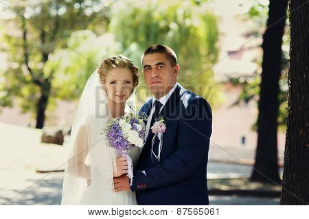 The Bride And Groom With A Bouquet Standing In The Park