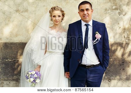 Bride And Groom Standing On Wall Background