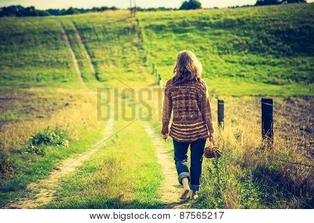 Girl In Sweater Walking By Rural Grassy Road