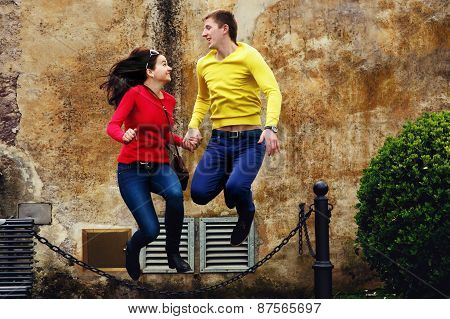 Loving Couple Running And Jumping Through The Chain