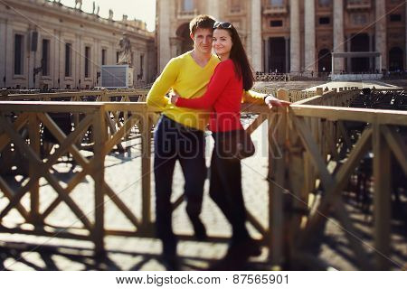 A Couple Of Tourists Standing Near The Fence On The Square At St. Peter's In The Vatican. Rome, Ital