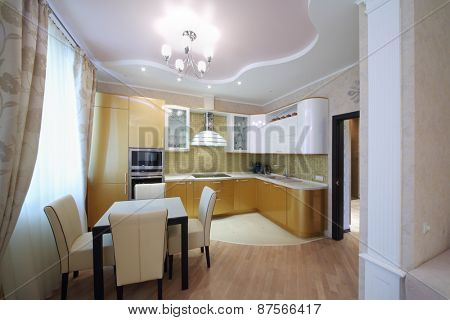 Interior of luxurious kitchen with golden cabinets in the apartment