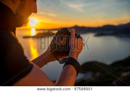 Man photographing sunset on the top of mountain