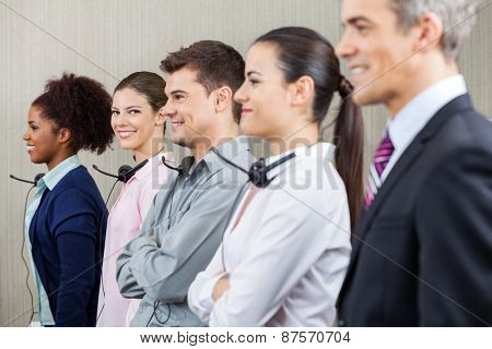 Portrait of smiling female customer service representative standing with colleagues and manager at call center