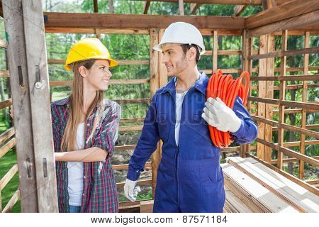 Smiling male and female construction workers in wooden cabin at site