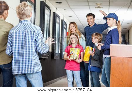 Man calling children while standing with family and worker at cinema