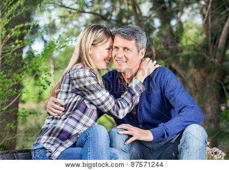 Portrait of happy man embracing girlfriend at campsite
