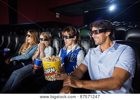 Family of four having snacks while watching 3D movie in cinema theater