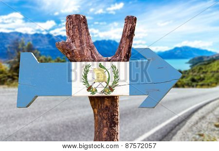 Guatemala Flag wooden sign with road background