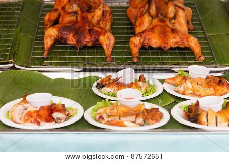 cooking, asian kitchen, sale and food concept - grilled or fried chicken on plate at street market