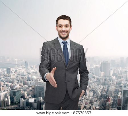 business and office concept - handsome businessman with open hand ready for handshake