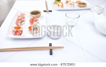 restaurant, food, people, asian and japanese kitchen concept - close up of woman eating sushi with chopsticks at restaurant