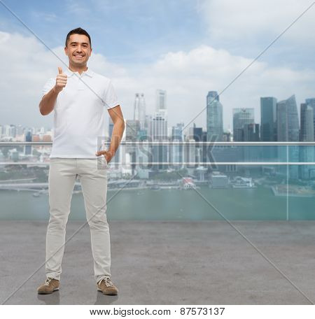 business, travel, tourism, gesture and people concept - smiling man showing thumbs up over city background