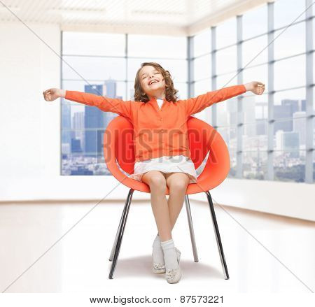 people, happiness, childhood and furniture concept - happy little girl sitting on chair with spreaded arms over empty living room background