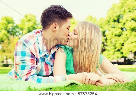 holidays, vacation, love and friendship concept - smiling couple kissing in park
