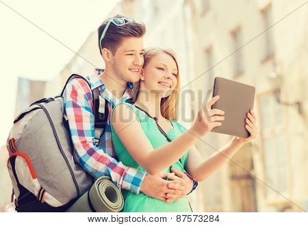 travel, vacation, technology and friendship concept - smiling couple with tablet pc and backpack in city