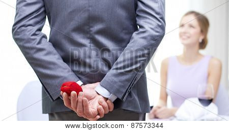 couple, love, proposal and holiday concept - close up of man hiding red box behind from woman at restaurant