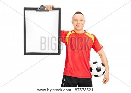 Young football player in a red and yellow jersey, holding a clipboard and a ball isolated on white background
