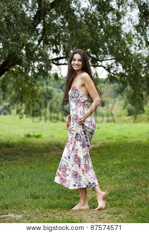 Sexy young brunette walking in summer park