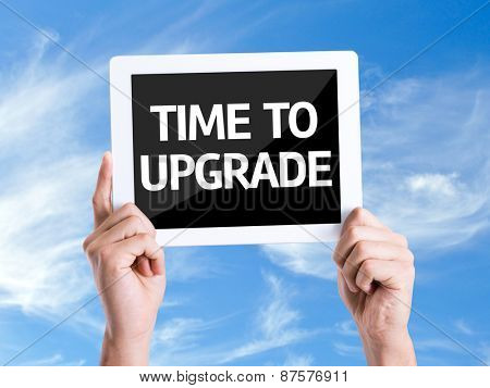 Tablet pc with text Time To Upgrade with sky background