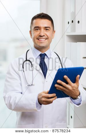 healthcare, technology, profession, people and medicine concept - smiling male doctor in white coat with tablet pc computer in medical office