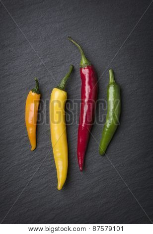 Colorful chili peppers arrangement, looking classy, isolated on dark grey slate stone plate.