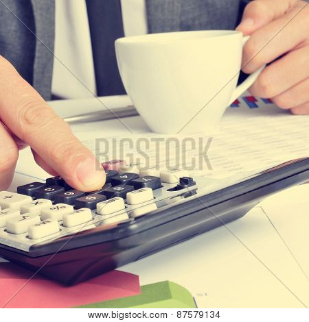 closeup of a young businessman with a cup of coffee in his hand checking accounts with a calculator at the office