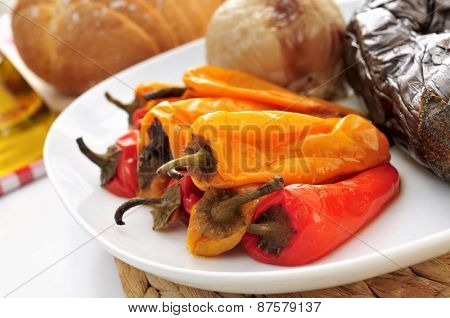 closeup of a plate with some grilled vegetables, such as onion, eggplant and peppers, on the kitchen table with a sliced loaf of bread in the background