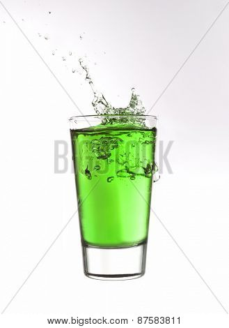Splash in a glass of green lemonade isolated on white background