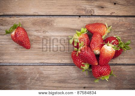 Top view of fresh strawberries on wooden background