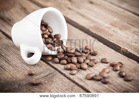 Cup with coffee beans on wooden background