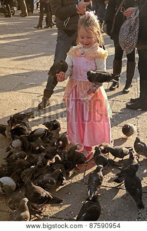Beautiful Girl On San Marco Square Feed Large Flock Of Pigeons In Venice, Italy.