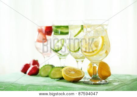 Glasses of different home made freshness healthy vitamin-fortified water on wooden table