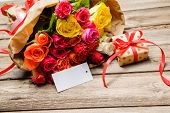 image of bunch roses  - Bunch of roses and gift box with an empty tag on wooden background - JPG