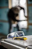foto of protective eyewear  - Protective Glasses and Utility Knife on a Table Saw with a worker in background - JPG
