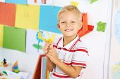stock photo of schoolboys  - Portrait of happy schoolboy with a paper crane - JPG