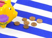 picture of greek  - An empty piggy bank on the Greek flag with small euro coins - JPG