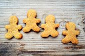 picture of gingerbread man  - Gingerbread cookies in shape of man on wooden table - JPG