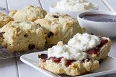image of racks  - Sultana Scones on a Plate Served with Jam and Cream with Rack of Scones in the Background and Bowls of Jam and Cream - JPG