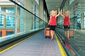 picture of children walking  - Blond smiling girl with her luggage standing on airport travelator moving to airplane departure gate vacation travel with children - JPG