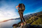 picture of vest  - Sports woman in red vest with backpack standing on the top of mountain on the sunset - JPG
