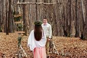 picture of wedding arch  - bride and groom in the wedding ceremony in forest near the decorate arch - JPG