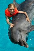 stock photo of swimming  - Little Smiling Girl Swimming with the Dolphin in the Swimming Pool in the Bright Sunny Day - JPG