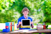 picture of school lunch  - Happy smiling school boy smart student holding a white touch screen tablet computer relaxing on a school yard lawn reading books playing games and having apple for lunch copy space for your text - JPG