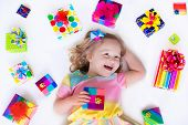 image of laugh  - Happy laughing little girl adorable toddler in a colorful party dress holding many birthday presents opening boxes decorated with ribbon and bow excited to celebrate a family holiday - JPG