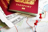 stock photo of boarding pass  - Boarding pass and passport on map with thumbtack concept for travel and vacations - JPG