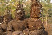 foto of serpent  - Stone Asura demons hold the naga serpent king Vasuki on the bridge entrance to Angkor Thom Cambodia - JPG