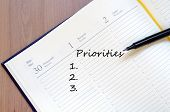 stock photo of priorities  - Priorities Concept In Yellow Blank Notepad On Office Wooden Table - JPG
