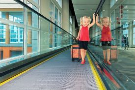 pic of gate  - Blond smiling girl with her luggage standing on airport travelator moving to airplane departure gate vacation travel with children - JPG